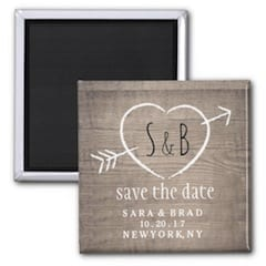 rustic save the date magnet with initials in a heart and arrow on a faux wood base
