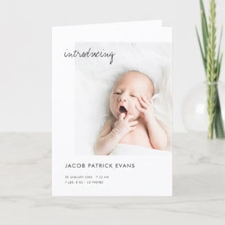 simple minimalist black and white birth announcement folded card with photo and 'introducing' in modern script